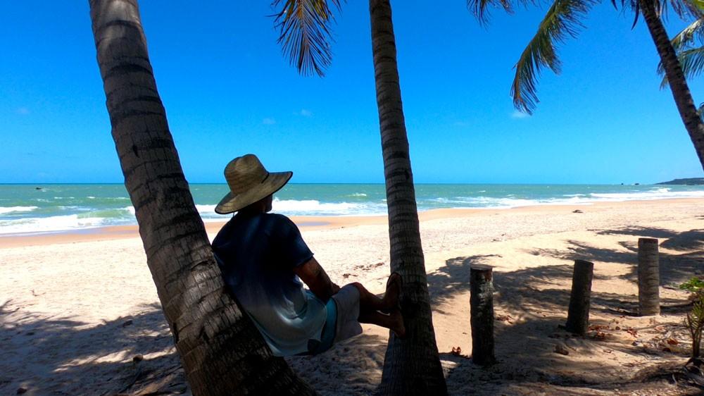 viajante sentado na areia com as pernas esticadas, apoiadas em uma árvore, em praia deserta no litoral Sul, durante o dia