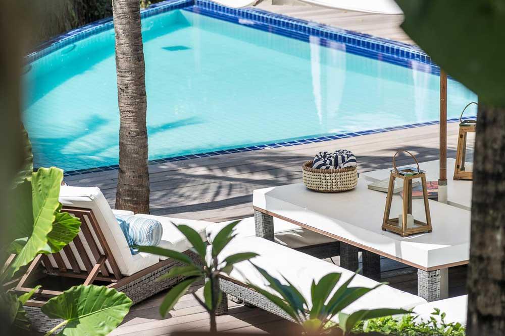 Espreguiçadeira e mesas em frente a piscina de Teju-açu uma ecopousada em Fernando de Noronha, um dos lugares para viajar a dois