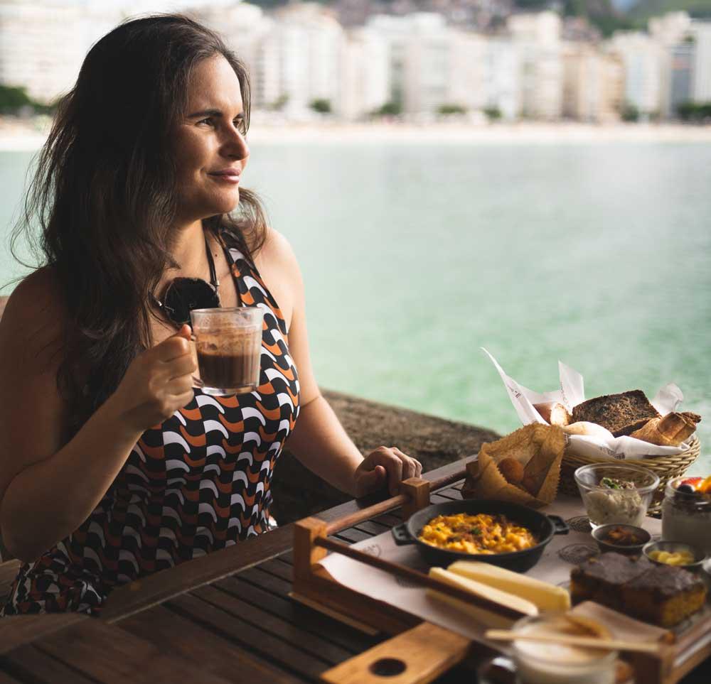 viajante toma café da manhã durante o dia, em frente ao mar, em viagem a dois
