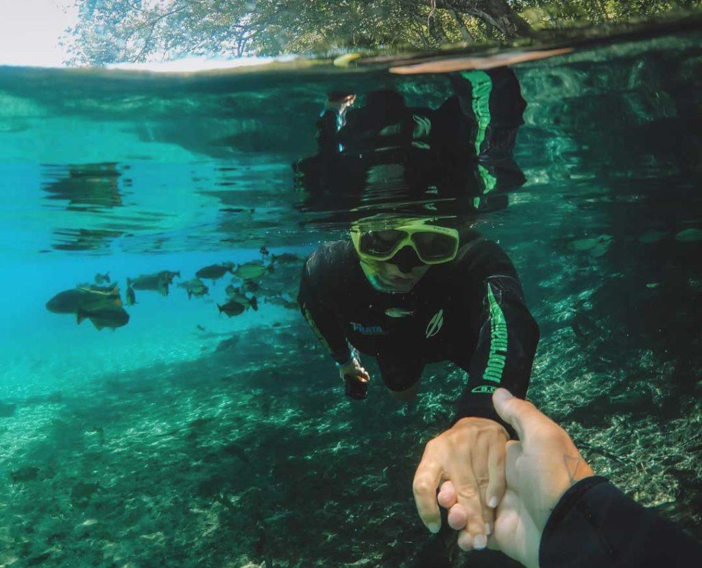 Mulher com equipamentos de mergulho debaixo d'água onde há peixes, dá a mão para outra pessoa em Bonito, um dos lugares para viajar a dois