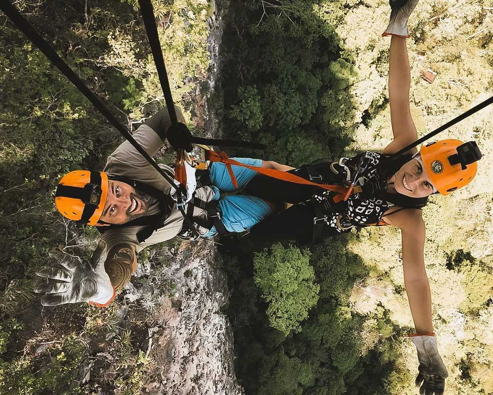 Vagner Alcantelado e Bárbara Rocha sorriem pendurados em corda de rapel acima de árvores, em Bonito, um dos lugares para viajar barato