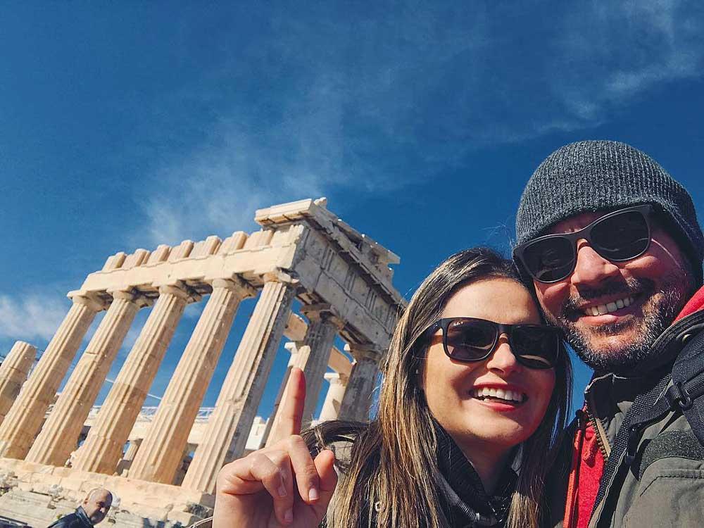 Viajantes sorriem em Grécia durante viagem a dois