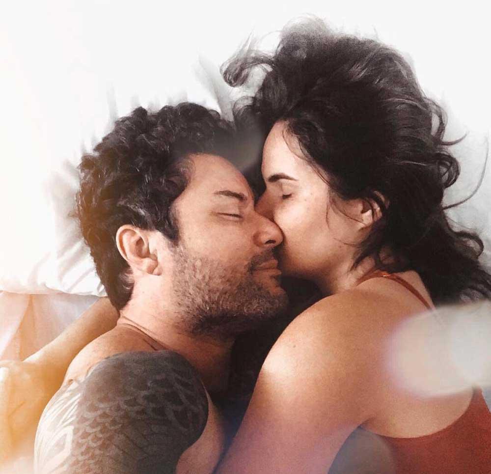casal se abraça em cama de hotel durante viagem a dois