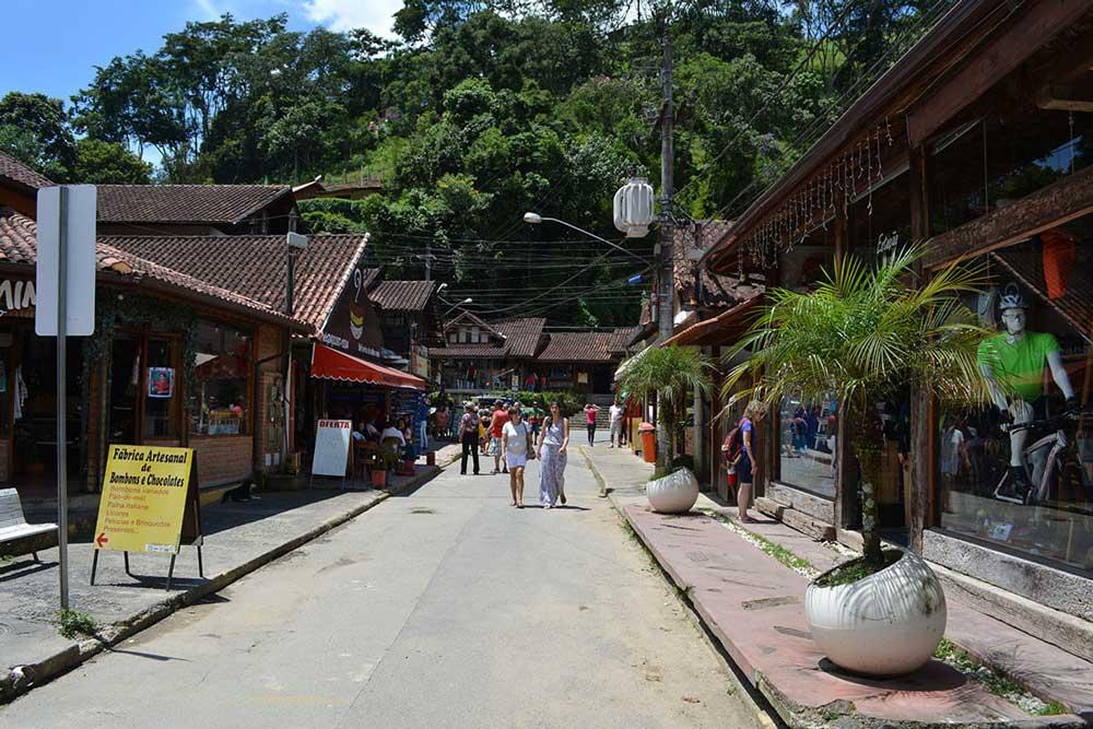 Viajantes caminham em ruas com lojas em Visconde de Mauá