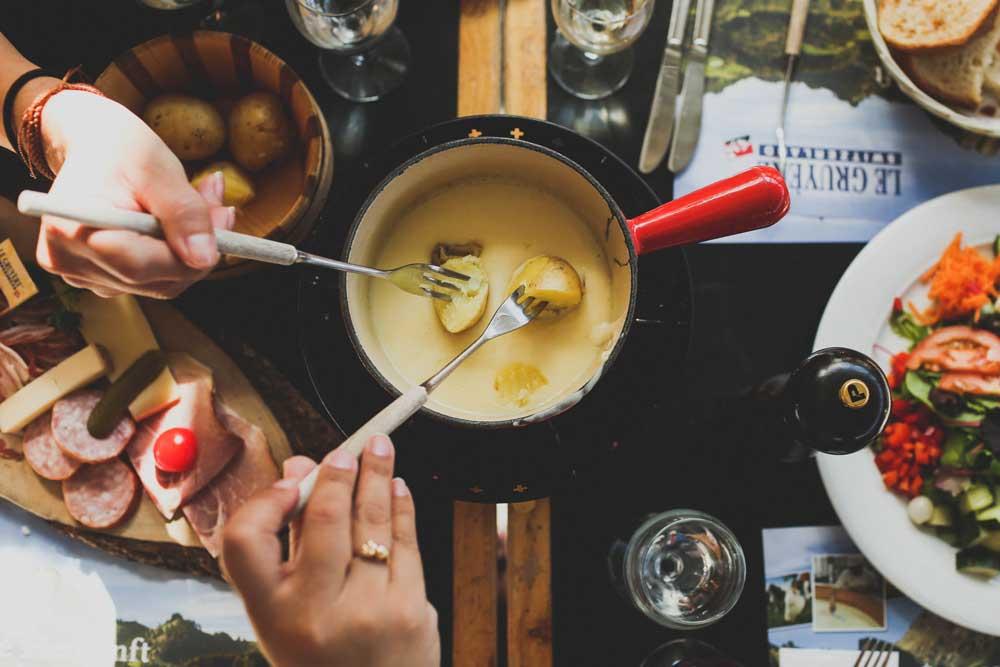 Pessoas espetam com garfo batatas em uma panela em cima de mesa preta em restaurante, onde há outros pratos de comida