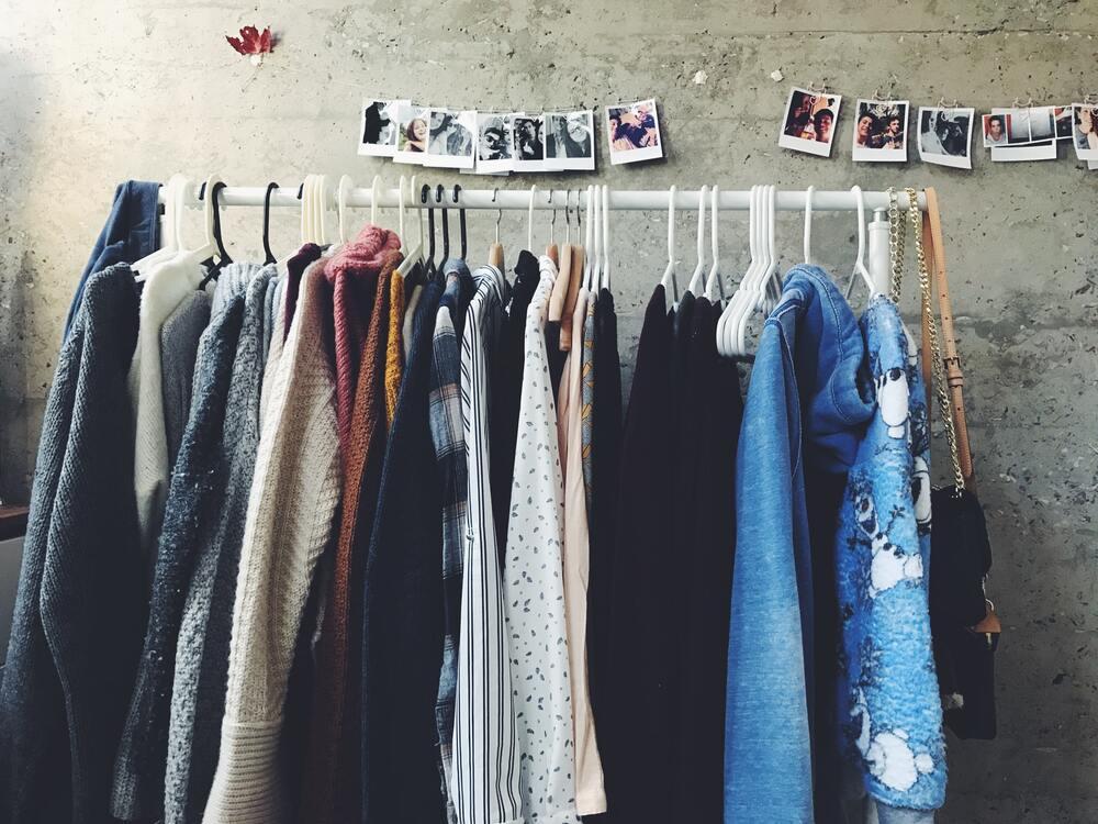 Arara de roupas em um brechó, um bom lugar para fazer compras, economizar e juntar dinheiro pra viajar