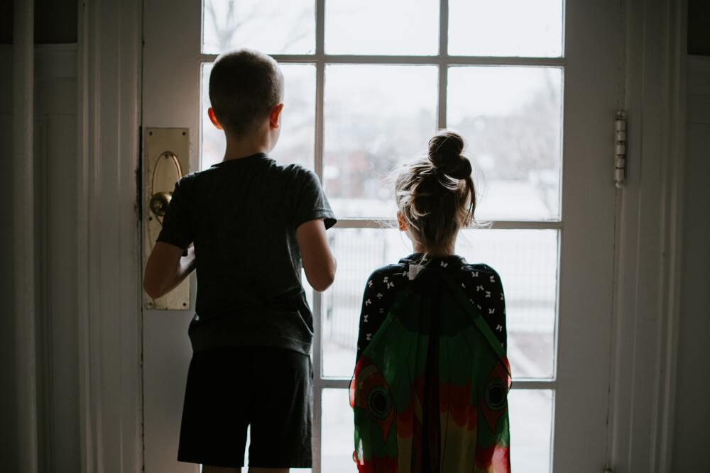 Crianças observam a rua pelo vidro da janela de casa