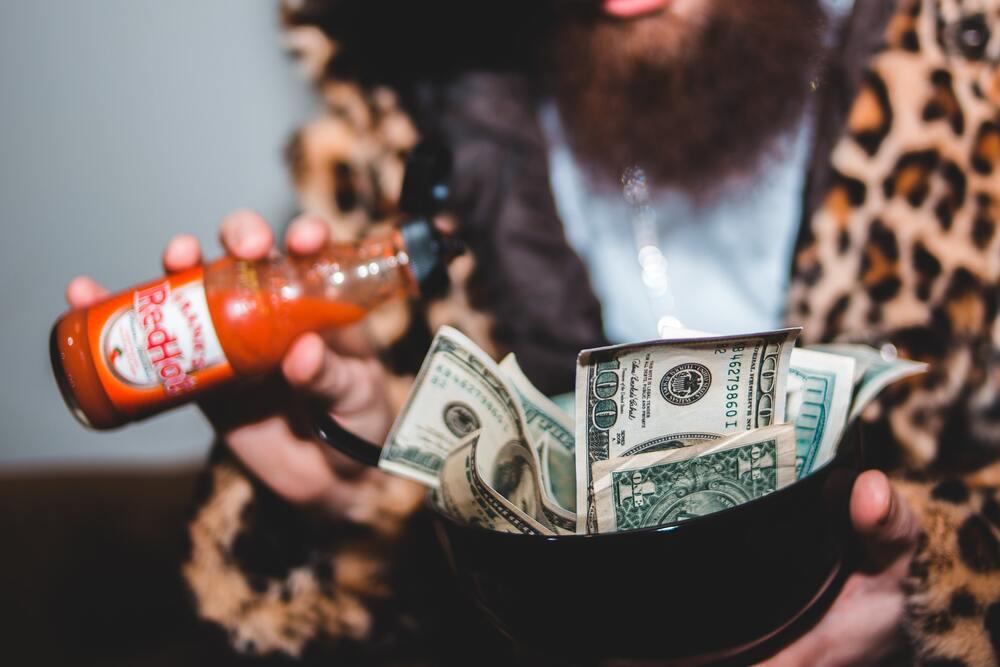 Homem segura tigela com várias notas de dólar