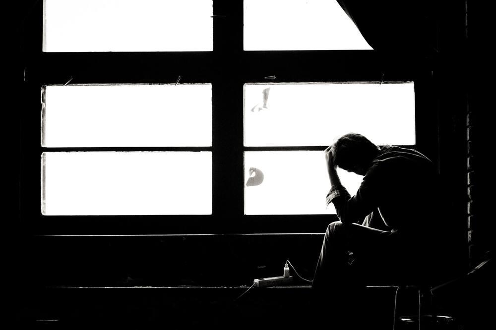 Silhueta de homem sentado com a mão na cabeça