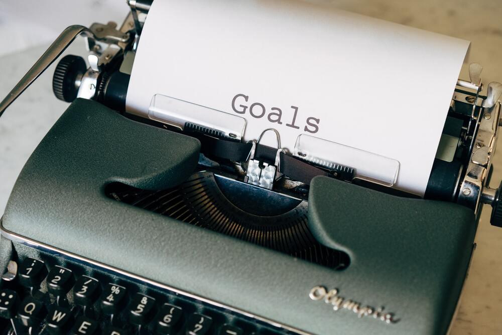 """Papel onde há escrito """"goals"""" (metas) saindo de máquina de escrever"""