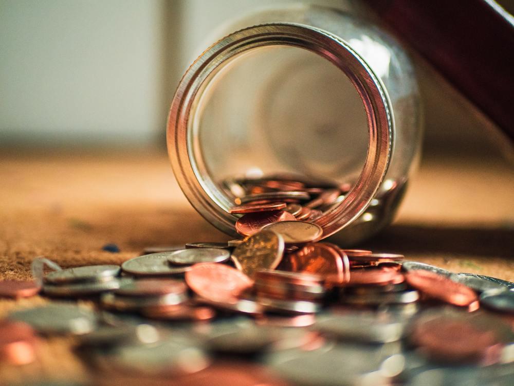 Moedas caem de um cofre, um objeto que pode ser usado para juntar dinheiro para viajar