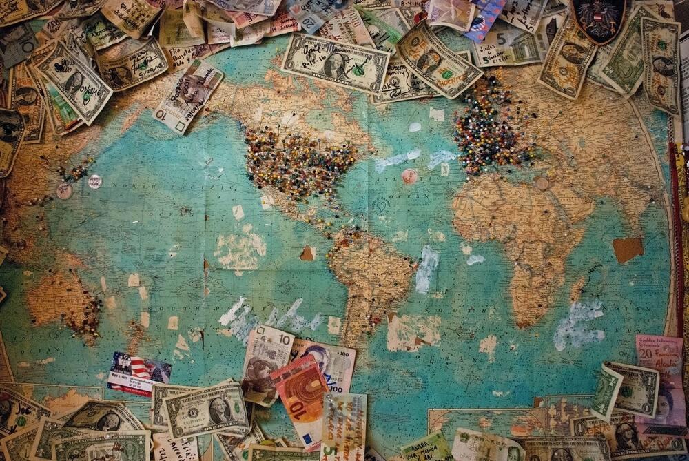 Notas dinheiro em cima de mapa mundil, que devem ser guardadas por quem quer juntar dinheiro para viajar