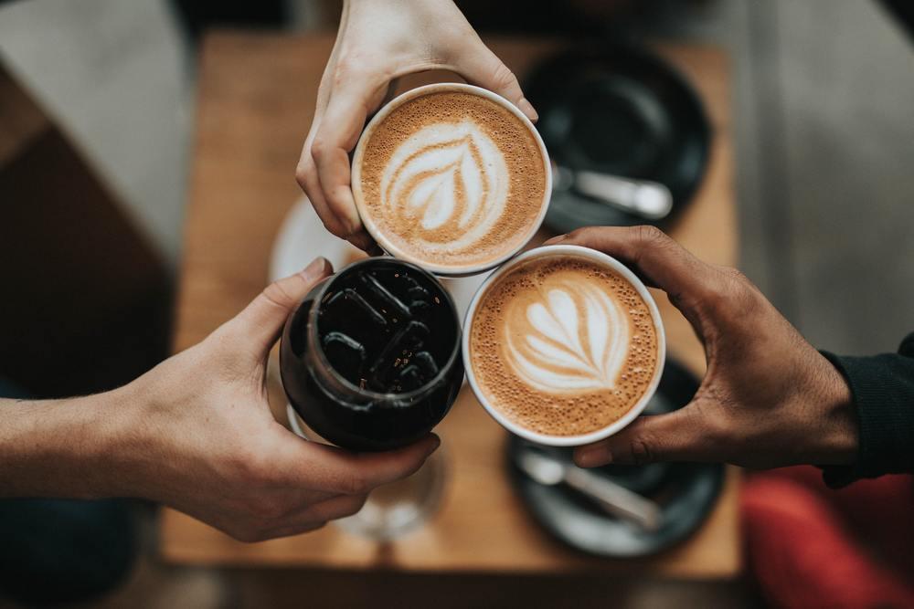 Pessoas brindam com café de cafeteria, que deve ser evitado por quem quer juntar dinheiro para viajar