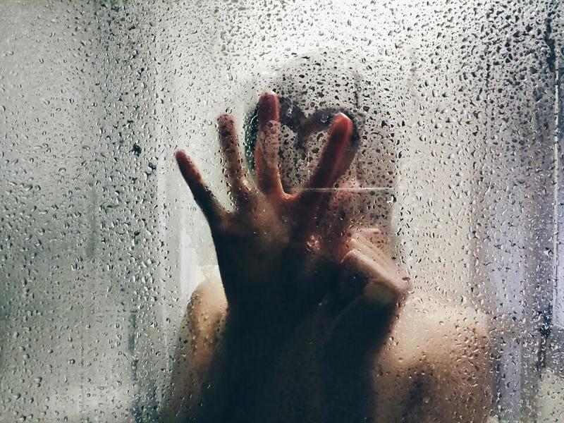 Pessoa tomando banho desenha coração com os dedos em vidro de box embaçado