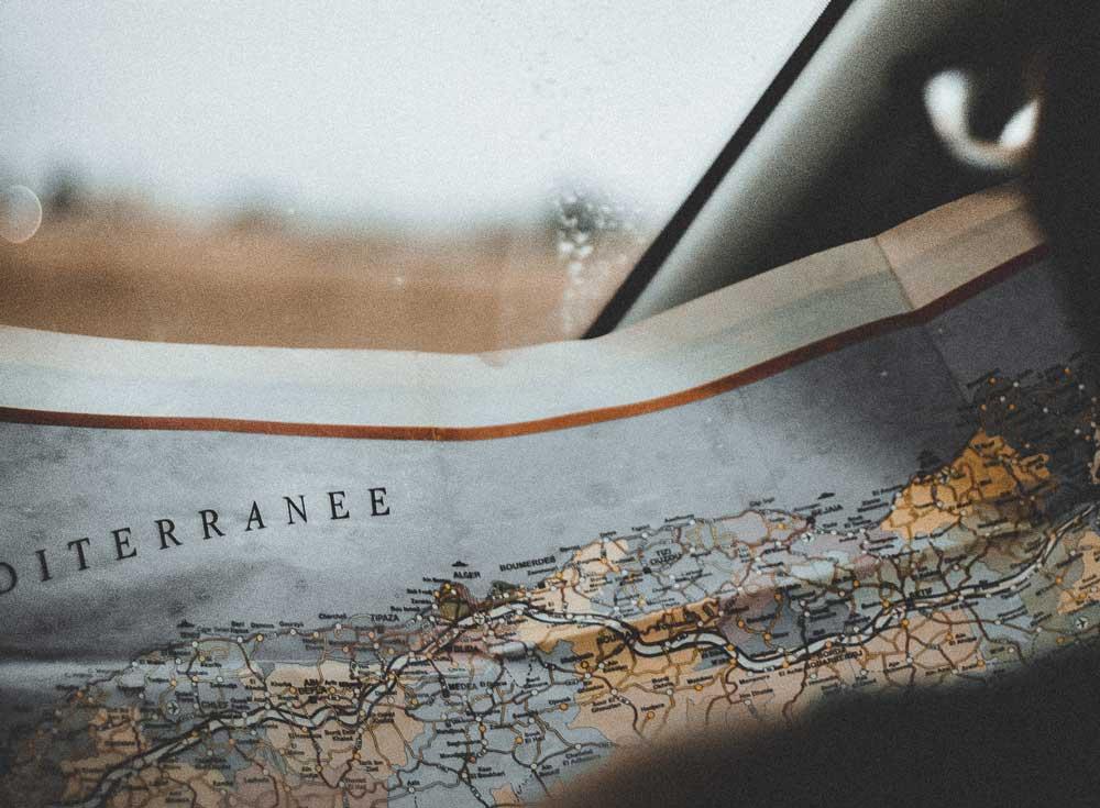 Viajante segura mapa de papel em carro durante viagem a dois