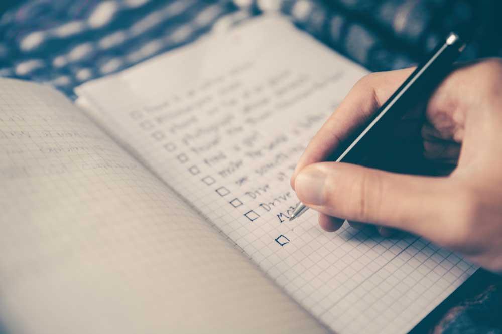 Pessoa anota em caderno dicas de viagem a dois