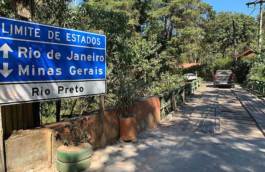 """Placa azul e branca em Visconde de Mauá onde há escrito ''Rio Preto'', e acima """"Limites de estado, Rio de Janeiro - Minas Gerais''"""