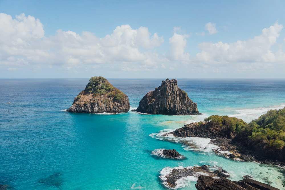 Vista aérea de águas cristalinas e pedras em praia em Fernando de Noronha, um dos lugares para viajar a dois