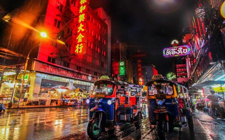 Pessoas em tuk-tuks em estrada molhada, durante a noite, onde há estabelecimentos com fachadas de letreiros coloridos iluminados