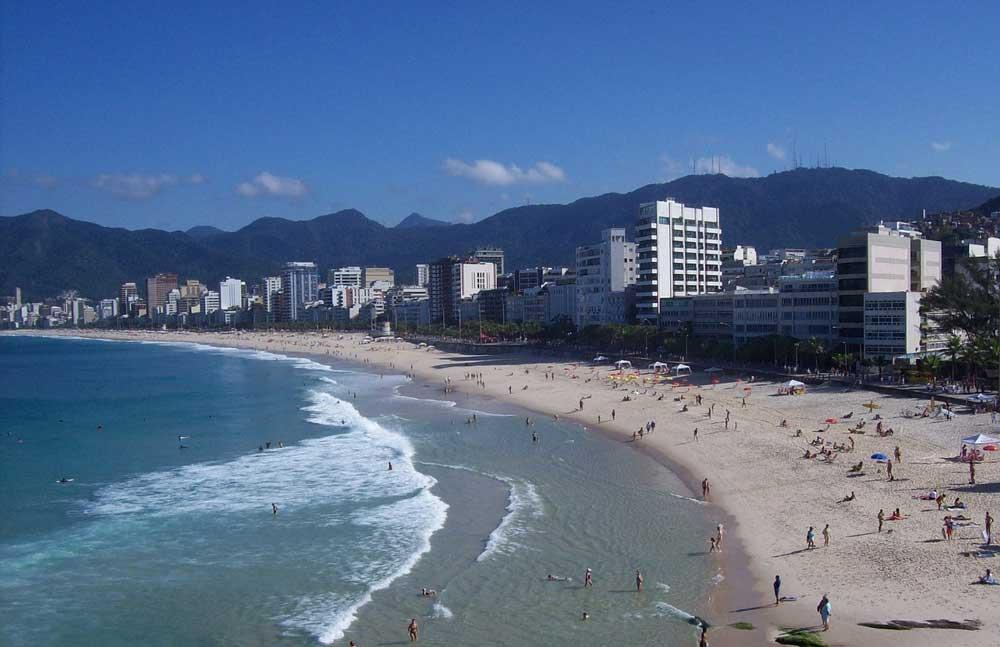 Pessoas na areia e no mar, em praia do Rio de Janeiro, durante o dia, um dos principais passeios do rj