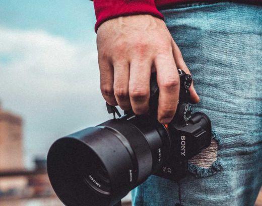 Fotógrafo segura câmera para fotografar, uma das formas de ganhar dinheiro viajando