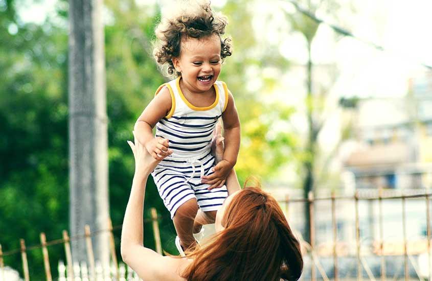Viajante Au Pair (uma das profissões para ganhar dinheiro viajando), brinca com uma criança sorridente