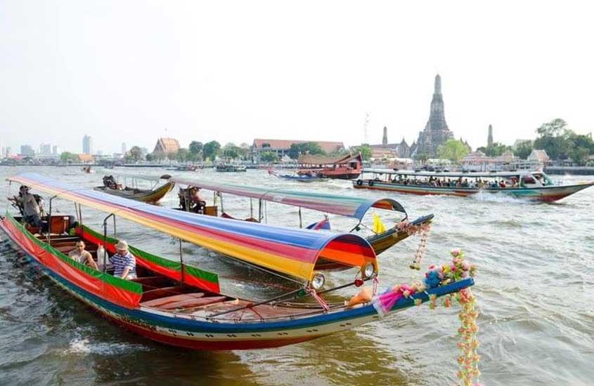 Pessoas em barcos coloridos, durante o dia, em rio Chao Phraya, em Bangkok, uma das opções de passeio para quem não sabe o que fazer em Bangkok em 3 dias