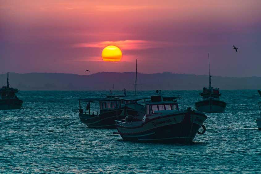 Barcos no mar de búzios durante o pôr do sol