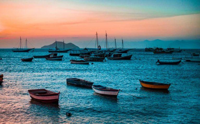 barcos atracados em praia de Búzios ao entandecer