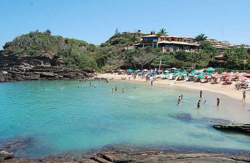 Turistas tomam banho de mar na Praia da Ferradurinha durante o dia