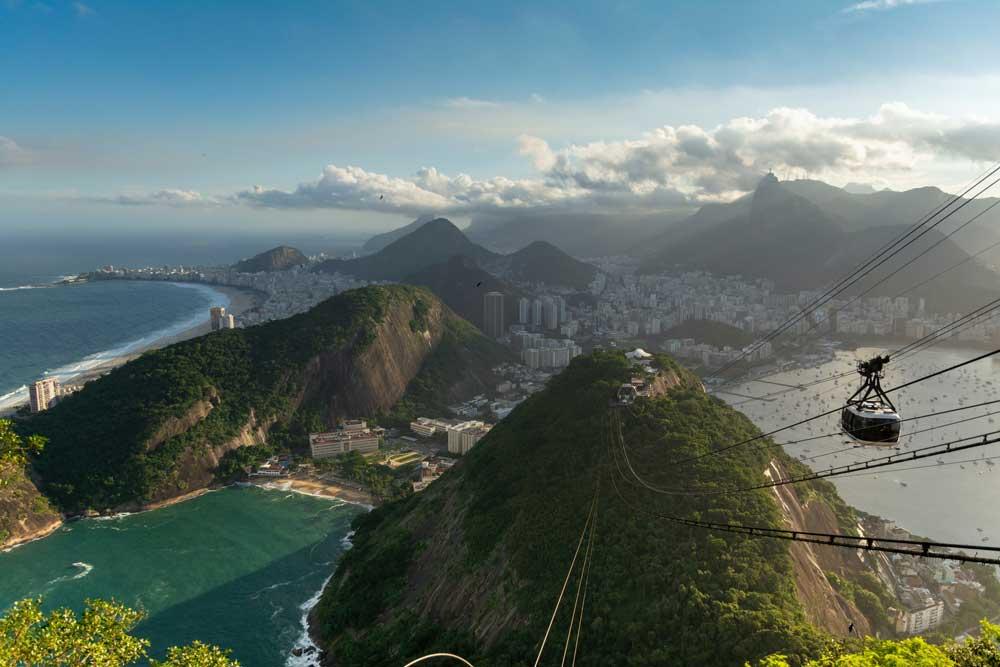 teleférico branco e preto passando em cabos que conectam o topo de duas montanhas, no Rio de Janeiro, durante o dia