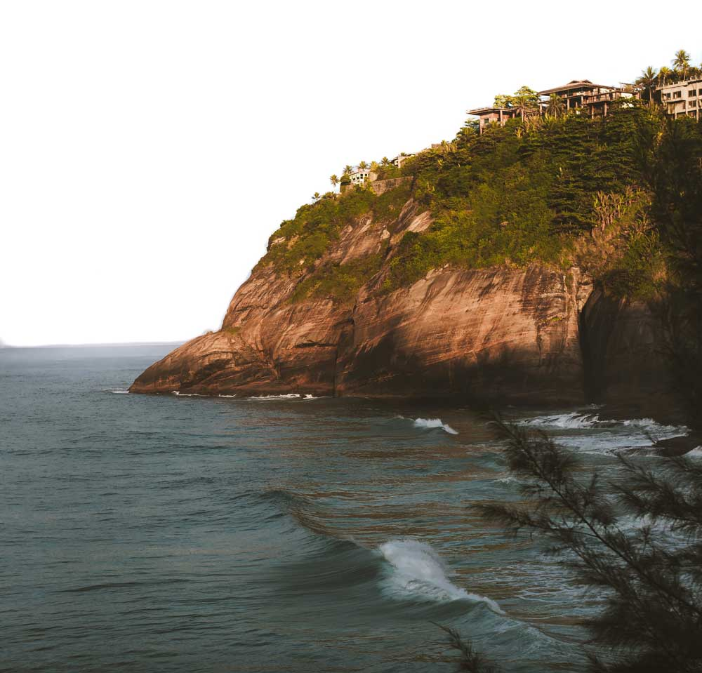 Montanha marrom e verde ao lado do mar, durante o dia, em Praia da Joatinga no Rio de Janeiro