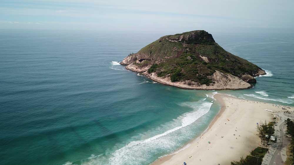 Vista área de mar e Pedra do Pontal, uma formação rochosa de com altitude de 125 metros, às margens da areia da praia do Recreio, no Rio de Janeiro