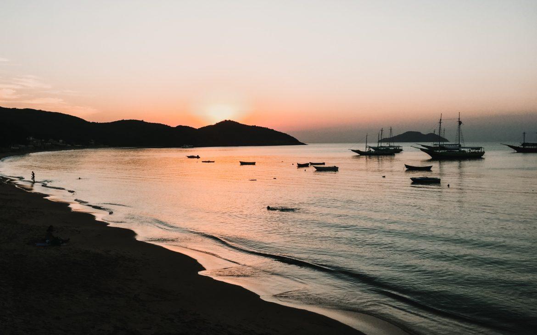 Vista panorâmica do nascer do sol sobre o mar, onde há barcos, em Búzios, cidade da Região dos Lagos.
