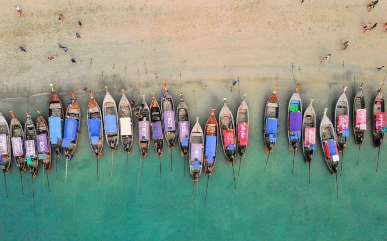 Vista área de bancos coloridos ancorados em praia na Tailândia durante o dia