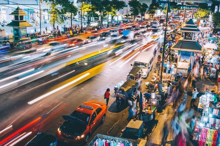Carros passam em estrada ao lado de calçadas movimentas com pessoas e barracas de comidas e roupas, durante a noite em Bangkok, a capital da Tailândia