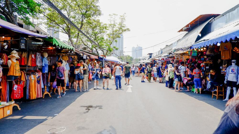 Pessoas caminham, durante o dia, em Cha Tu Chak Market, mercado em Bangkok, capital da Tailândia Tailândia