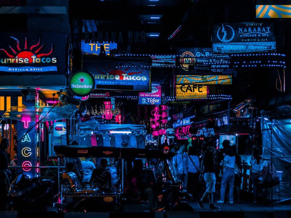 Tuk-tuk passa em frente à rua movimentada de pessoas, a noite, em Bangkok