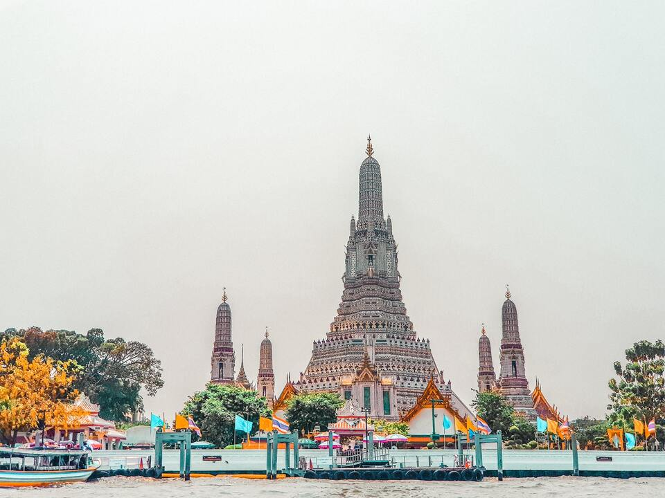 Construção branca e cinza, sob o céu nublado, conhecida como Wat Arun o Templo do Amanhecer, em Bangkok