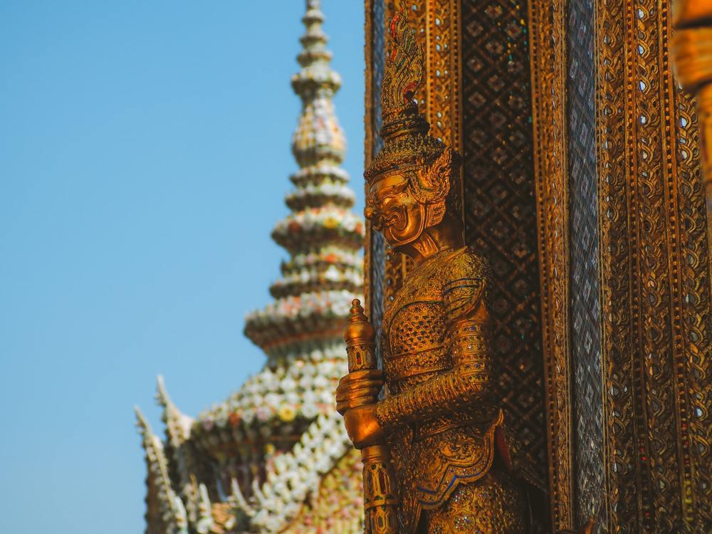Estátua de homem dourada em frente a templo, durante o dia, em Bangkok, a capital da Tailândia