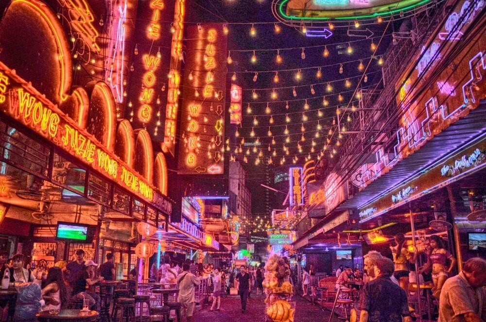 Pessoas caminham em rua iluminada com luzes vermelhas e amarelas, durante a noite, em Soi Cowboy, um dos famosos distritos da luz vermelha em Bangkok