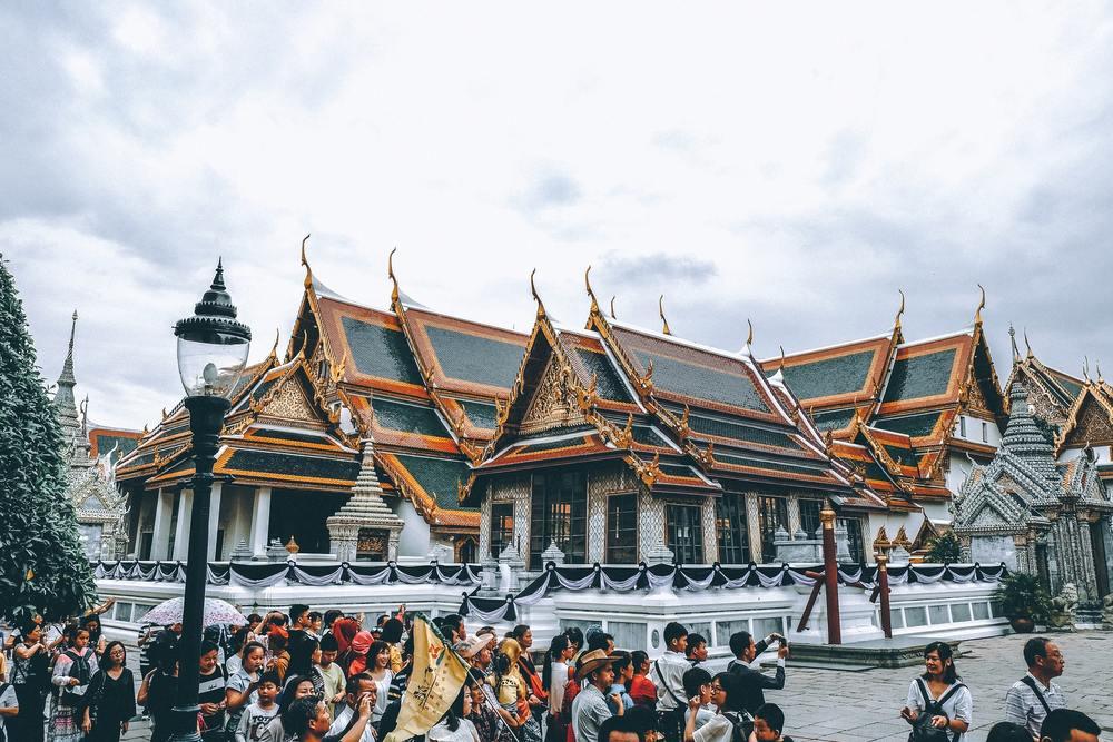 Tailandeses em frente a templos em Bangkok, capital da Tailândia, durante o dia
