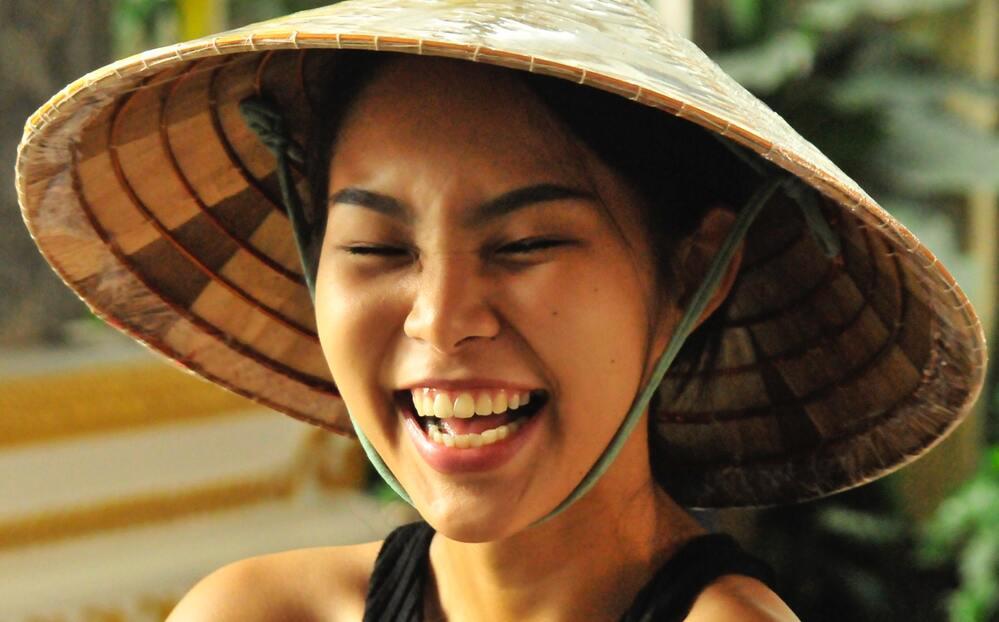 Mulher tailandesa com chapéu, sorri de olhos fechados