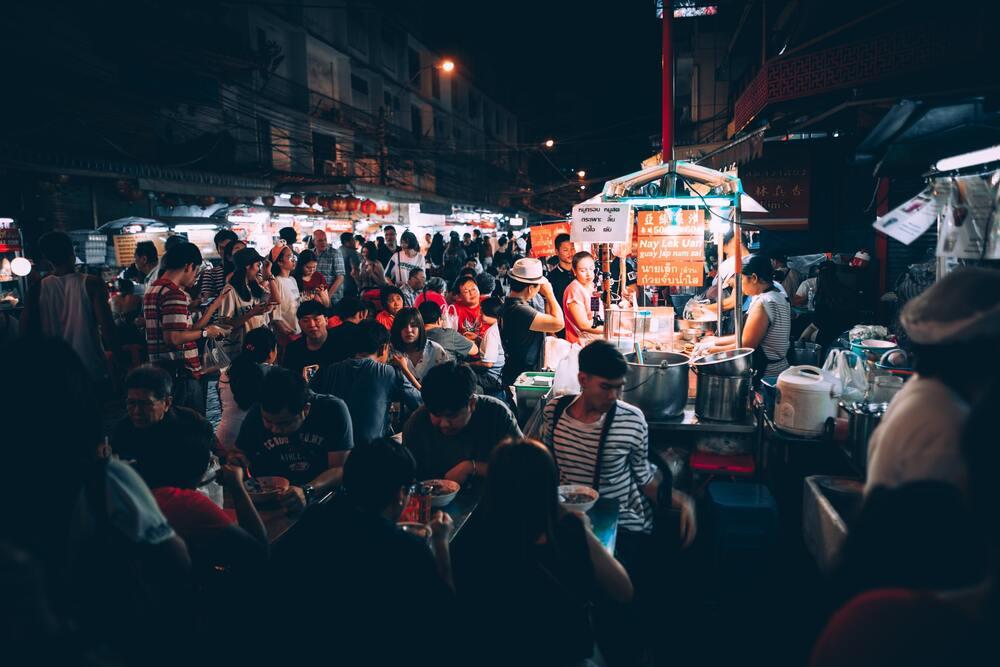 Pessoas comendo em barracas de comidas de rua em Bangkok, capital da Tailândia, durante a noite
