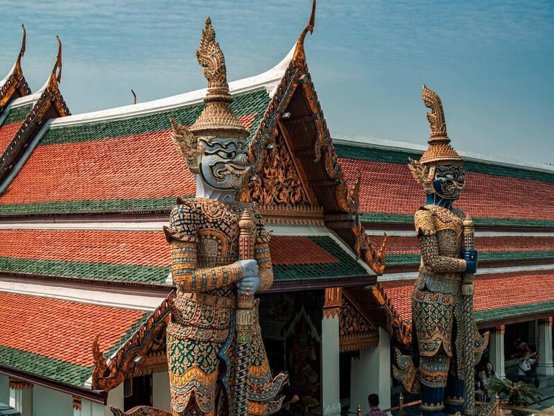 Estátuas gigantes coloridas em frente a Grande Palácio Real em Bangkok, capital da Tailândia, durante o dia