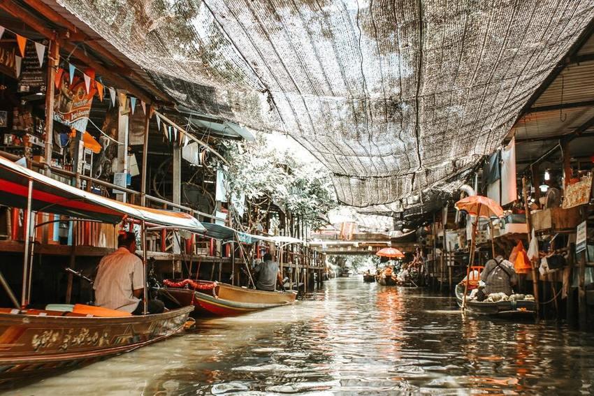 Pessoas andando de barco no rio, durante o dia, perto do mercado flutuante um dos principais atrativos de Bangkok