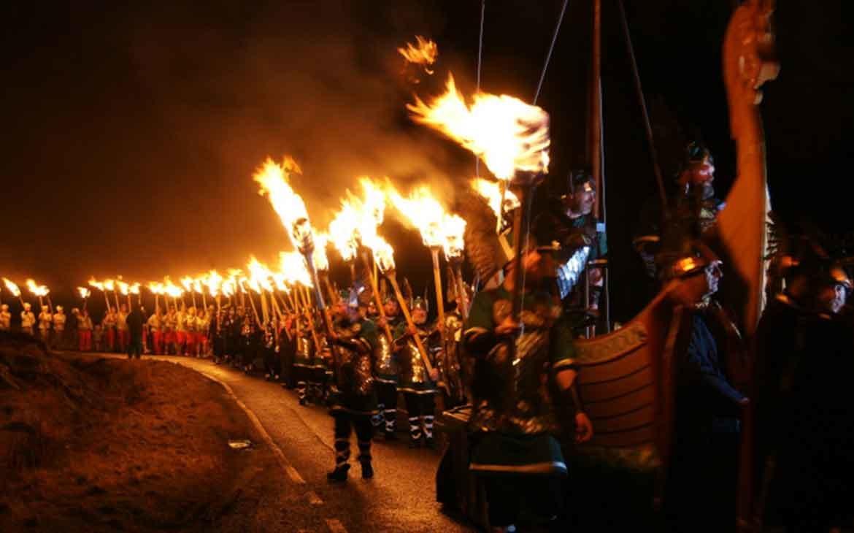 Homens vestidos como vikings, segurando tochas de fogo, caminham em procissão do festival Up Helly Aa