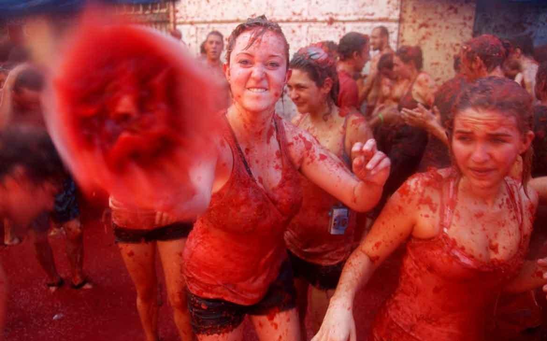 Mulher suja de tomate, joga tomate em direção a câmera durante La Tomatina, um dos festivais pelo mundo que ocorre na Espanha