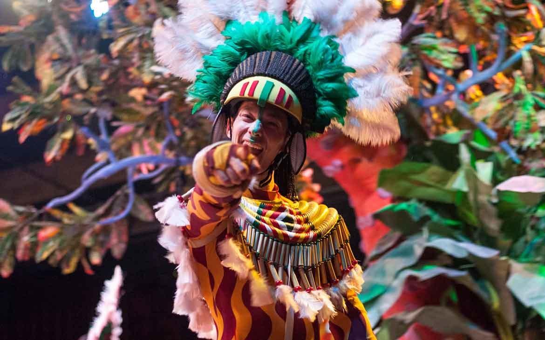 Homem com chapéu de penas e roupa com estampa de girafa aponta o dedo indicador para frente e sorri em meio ao Carnaval no Rio de Janeiro