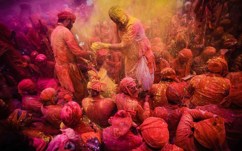 Pessoas com roupas sujas de pó rosa, jogam pó amarelo uma nas outras em Holi um festival que acontece na India